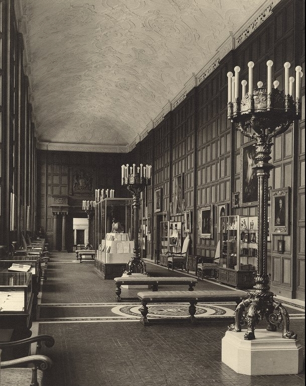Long room with wooden paneling and decorative plaster ceiling