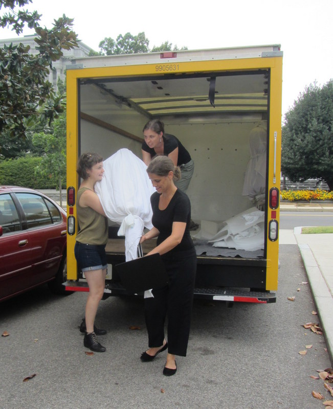 Lorenza Lattanzi, Caryn Lazzuri, and Rhea DeStefano unload a shrouded costume.