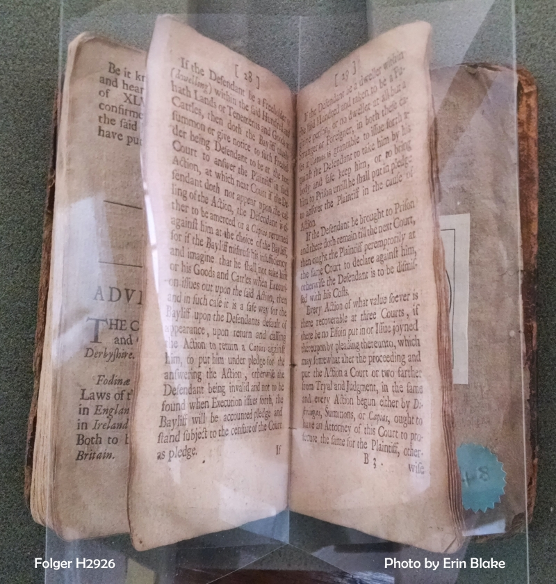 Brittle pages held open by a folded sheet of polyester film.