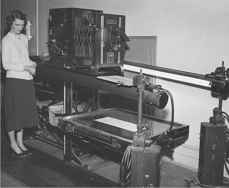 Woman standing next to large photographic apparatus