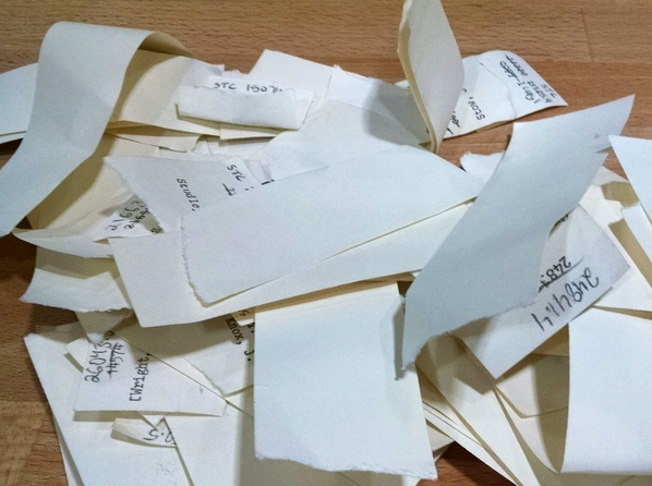 Pile of slips of paper with crossed out and handwritten STC numbers