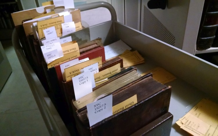 Row of about a dozen books with new call number flags and old call slips.