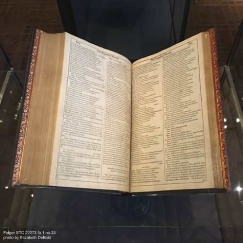 a first folio resting on a cradle in a display case, open to about 3/4 of the way through