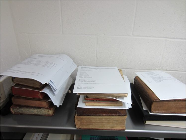 Three small stacks of books, with papers on top.
