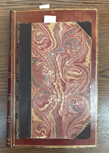 two volumes in 19th century bindings, lying on a table. The smaller one is atop the larger.