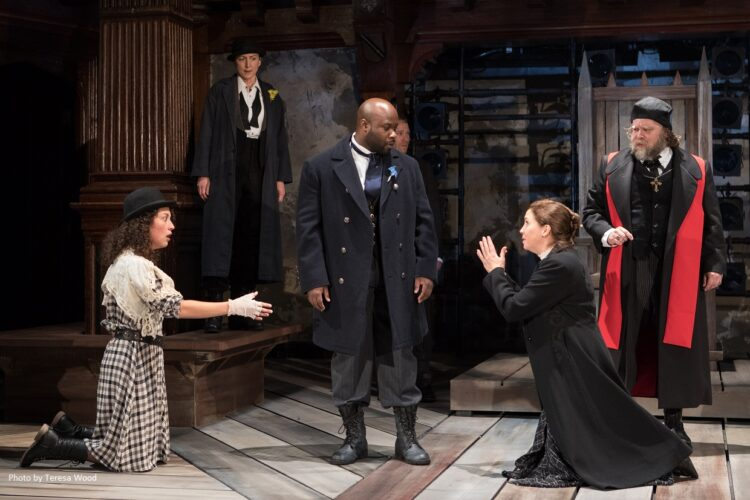 Scene from Folger Theatre's King John: Kate Eastwood Norris as the Bastard, Philip Faulconbridge (left, rear); Akeem Davis as Louis the Dauphin (center); Holly Twyford as Constance (kneeling, right)