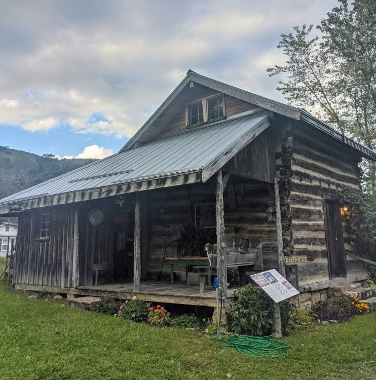 Small log cabin style house with a covered porch