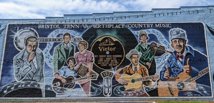mural painted on the side of a building depicting 7 people associated with the birth of country music. Some are standing around stand microphones, some are holding instruments